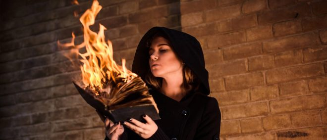 Young woman with burning book in hands (Shutterstock/Mikhail Klyoshev)